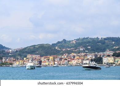 Boat on blue water on a background of mountains vacation summer sunny Bright houses italy