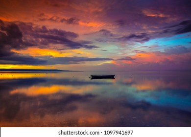 A boat on a calm beach with a surreal sunset at Walakiri Beach, East Sumba, Indonesia