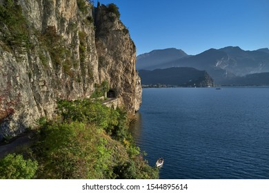 A boat on a cliff view of the city of Riva del Garda, Italy. Panoramic view of Lake Garda in the foreground, the city is surrounded by rocks and alpine mountains. Autumn season.