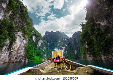 Boat on green Lake with perfect sky at Ratchaprapa dam, Khaosok National Park, Thailand