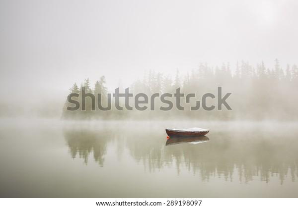 Bateau sur le lac au brouillard matinal.