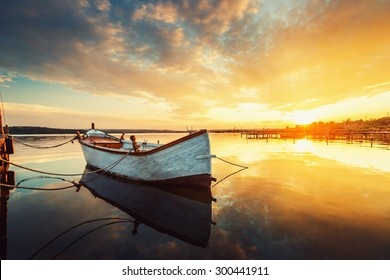 Boat on lake with a reflection in the water at sunset