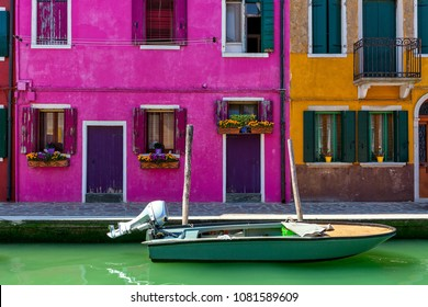 Boat on narrow canal in front of colorful houses of Burano, Italy.