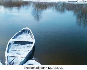 boat on the river in winter tied to the shore