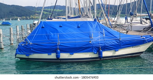 a boat on a sailing ship harbor covered with a blue cover