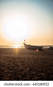 boat on a sand beach at sunset