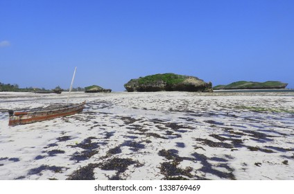 boat on the sand of watamu beach. In the background the shore and a large islet