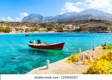 Boat on sea in Lefkos port with fishing nets on shore, Karpathos island, Greece