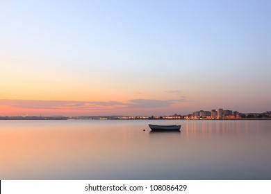 Boat on the tejo river and the city on background.