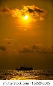 Boat on texture of tropical sea water and wave in golden light of sunset.