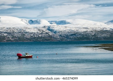 Boat on the water in Lyngen fjord with beautiful mountains in the background.