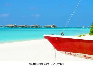 Boat on the white sand beach at maldives island