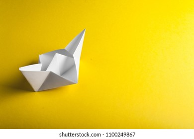boat paper origami on the yellow background. studio shot