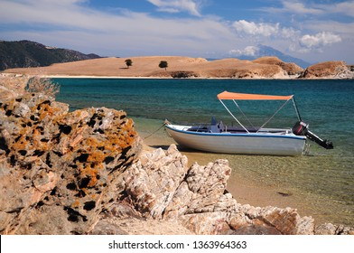 Boat parked in a crystal clear water lagoon of Ammouliani island, Halkidiki, Greece with mount Athos on the background.