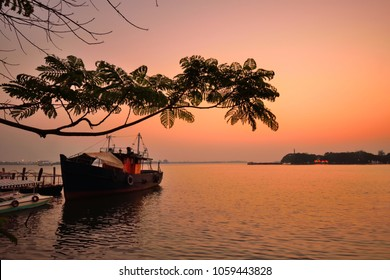 A boat parked in a jetty in Vembanad Lake in Marine Drive, Kochi during sunset.