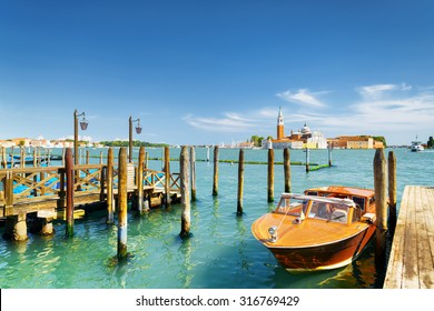Boat parked at pier beside the Riva degli Schiavoni on the Venetian Lagoon in Venice, Italy. The Church of San Giorgio Maggiore on island of the same name is visible in background.