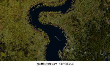 A boat passes through the seemingly  endless Palatlakaha River in Clermont, FL known for its plentiful fishing spots.