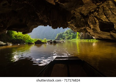 A boat passes through Tam Coc, a flooded cave at the Trang An UNESCO World Heritage site in Ninh Binh, Vietnam