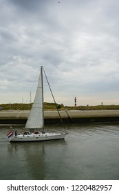 Boat passing lighthouse and entering the harbour of Nieuwpoort West Flanders Belgium