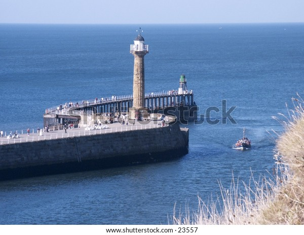 Boat passing lighthouse at entrance to Whitby Harbour, Yorkshire.