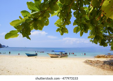 Boat, and people snorkeling near the beautiful beach under the blue sky