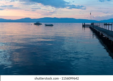 Boat pier and lake surface during early morning sunrise over Lake Tahoe in California