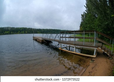Boat pier on a forest lake on a rainy summer day