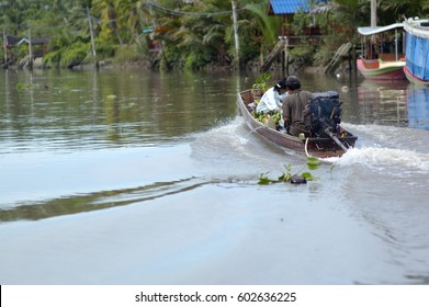 Boat POV Passing Riverside Houses In Tropical Landscape