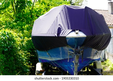 boat protected by blue tarp protective cover tarpaulin jacket on car trailer