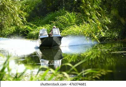boat racing on the river with people speed. The river, with the lush green vegetation around,  spray from under the boat. Natural summer background.