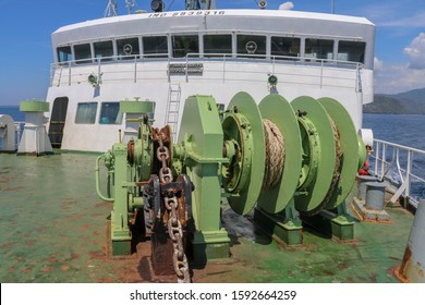 Boat reels with forecastle in background on a ferry in Indonesia. Electrically powered mechanisms for lowering the anchor and winding the mooring ropes. Strong chains and marine ropes and steel ropes.