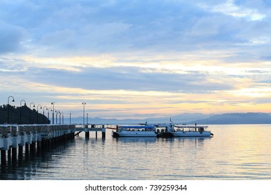 Boat resting near a jetty with sunrise background