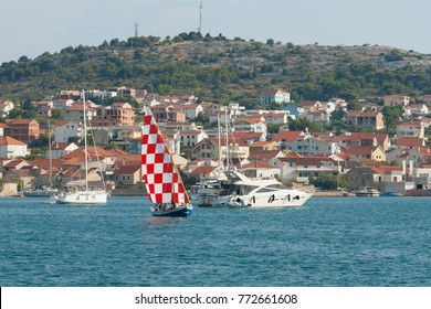 Boat with the sail of Croatian national colors. Archipelago in Adriatic.