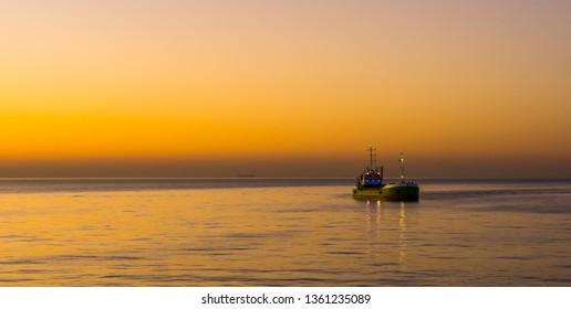 boat sailing at the belgian coast of Blankenberge during sunset, the sea of Belgium