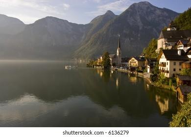 Boat sailing into the morning fog Hallstatt, Austria