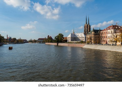 Boat sailing on the Oder river alongside the Cathedral Island in Wroclaw on a sunny day under the blue sky with white clouds