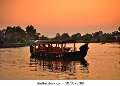 A boat sailing over alleppey backwaters during sunset.