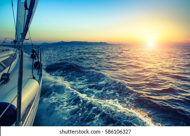 Boat in sailing regatta during sunset.