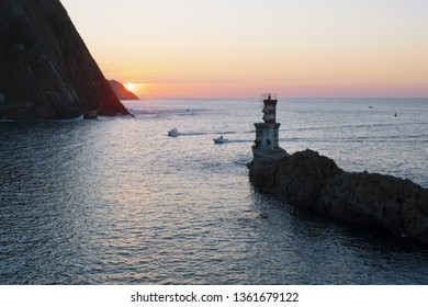 Boat sailing at sunset with mountains, Basque Country.