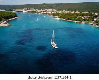 Boat sailing through blue waters of Adriatic sea, Aerial view shot on drone in Croatia.