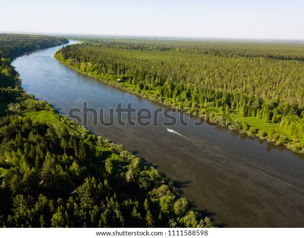 Boat sails along the river. Ob river flows through the taiga. River landscape, beautiful sky reflection in water. Vasyugan Swamp from aerial view. Tomsk region, Siberia, Russia