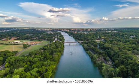 A boat sails down the Brazos River with the skyline of Waco, Texas sitting behind.