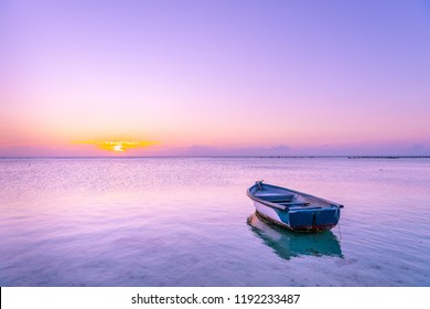 Boat in the sea with pink and purple colors during Sunset in beautiful Mauritius paradise landscape. Mauritius nature view of colorful sky and light of sun. Reflection on the sea near beach