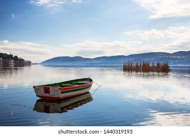 Boat with seagulls in the beautiful lake Orestiada against mountains and Kastoria city background. Kastoria is a city in northern Greece.