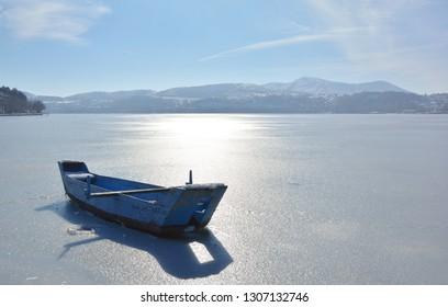 Boat in snowy lake of Kastoria in Greece