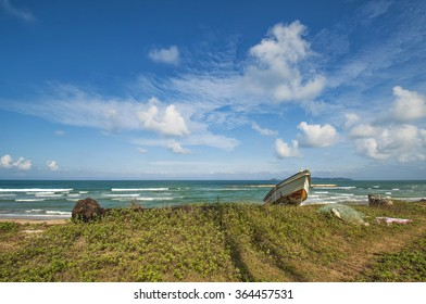boat stranded at the beach in sunny day with stunning clouds and blue sky