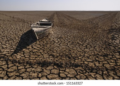 Boat stranded in the desert, Little Rann of Kutch, Gujarat, India. During the summer this area is flooded and fishing takes place in the dry winter months salt production is carried out.