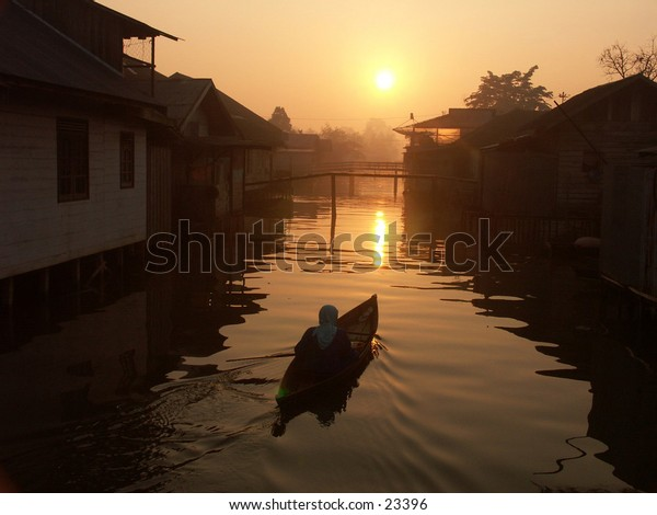 Boat and sunrise at South Borneo River, Indonesia.