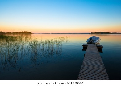 Boat in Sunset on Calm Lake in Finland