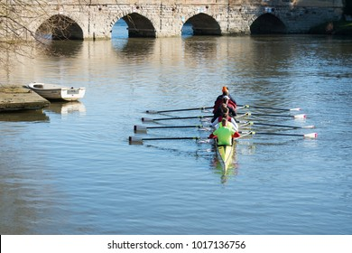 boat team rowing in front of bridge arches